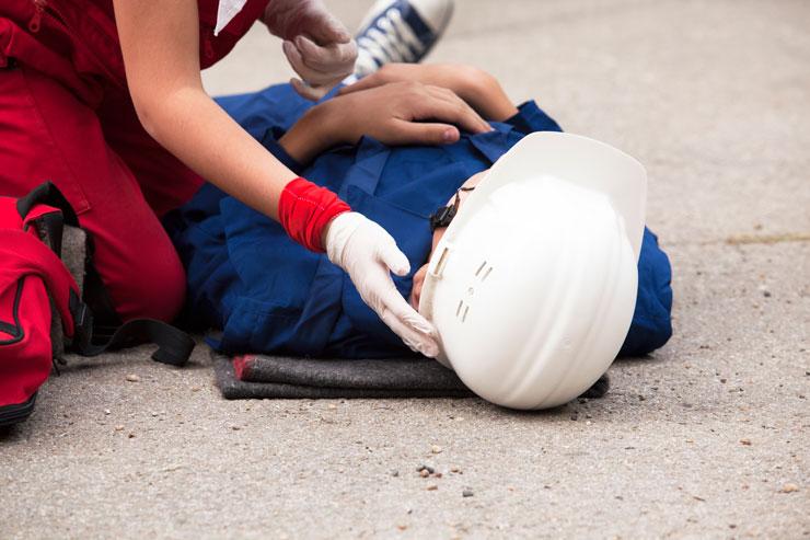 Homem caído com capacete - direitos do trabalhador acidentado