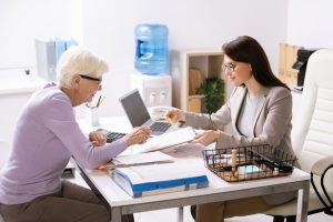 Pretty young female agent helping senior client to fill in insurance document