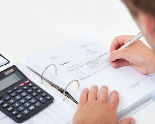 Cropped image of businessman calculating tax at desk in office